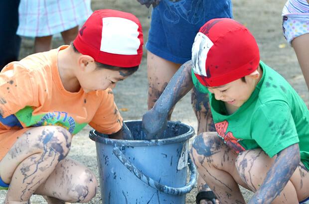 泥だらけで遊ぶ園児たちの写真